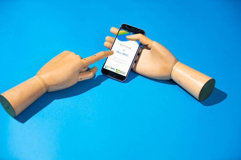 Mãos de madeira seguram celular com o aplicativo Meu INSS aberto.
