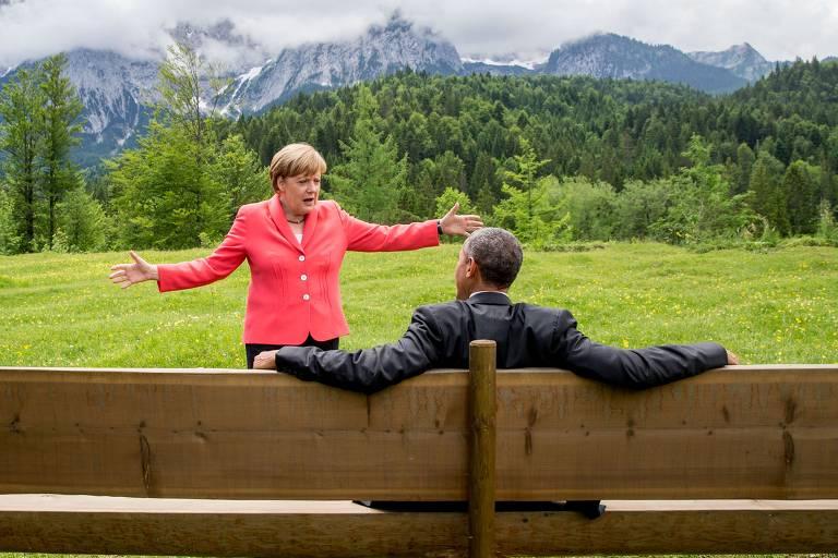 A chanceler alemã, Angela Merkel, gesticula enquanto conversa com o então presidente dos EUA, Barack Obama, sentado em um banco do lado de fora do Castelo de Elmau, após uma sessão da cúpula do G7, perto de Garmisch-Partenkirchen, na Alemanha