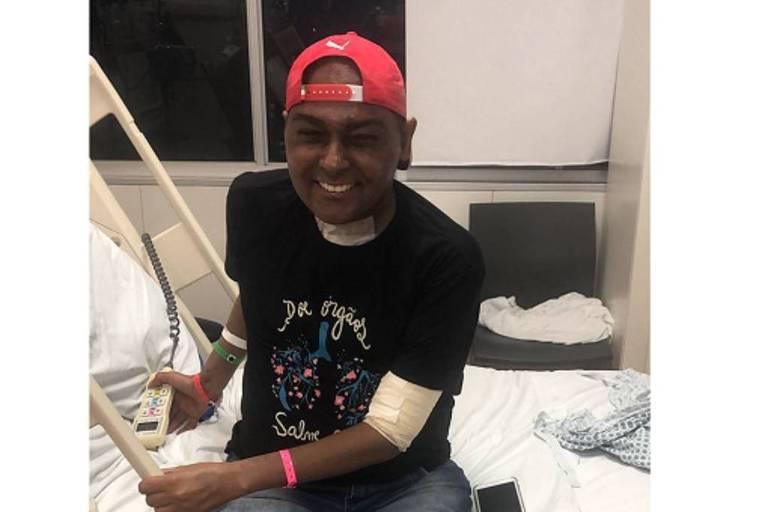 Paciente com bonê vermelho sorri sentado no leito de hospital