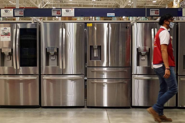 Quatro geladeiras prateadas estão colocadas lado a lado em um corredor, com preços delas destacados em placas em painéis acima delas. Um homem de calça jeans, camiseta branca, colete vermelho e máscara branca caminha por esse corredor.