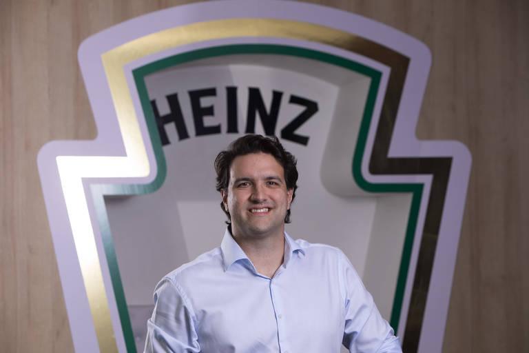 Homem branco sorri com logo da Heinz ao fundo