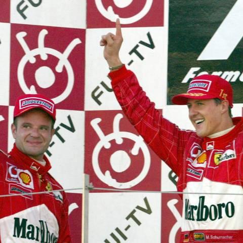 Automobilismo - Fórmula 1 - Grande Prêmio do Japão, 2002: o alemão Michael Schumacher (direita) e o brasileiro Rubens Barrichello, pilotos da Ferrari, comemoram a conquista dos primeiro e segundo lugares, respectivamente, no GP. Germany's Michael Schumacher (R) celebrates with his Ferrari teammate and second placer Brazilian Rubens Barrichello after winning the Formula One Japanese Grand Prix at Suzuka Circuit in Suzuka, Japan October 13, 2002. Schumacher clocked one hour 26 minutes 59.698 seconds. REUTERS/Toshiyuki Aizawa