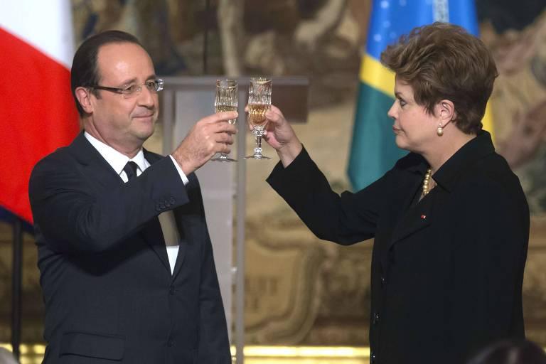 François Hollande está de terno e gravata escuros e camisa branca; ele brinda com uma taça com Dilma, que está de tailleur escuro, brindando e olhando para ele. Ao fundo, as bandeiras da França e do Brasil