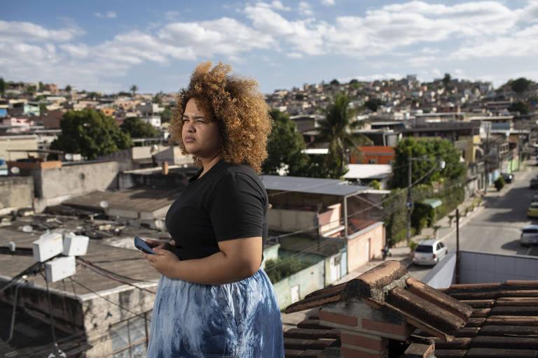 Dé pé, segurando um celular, Beatriz Menezes, moradora de São João Meriti na Baixada Fluminense