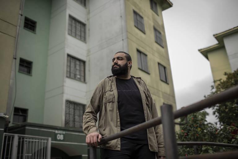 Felipe Freire Silva, que mora em um conjunto habitacional na zona sul de São Paulo, de pé, ao lado de um prédio da região