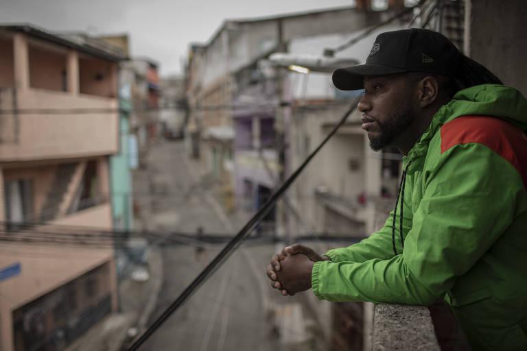 Kaique Pereira Martins, que mora na comunidade de  Heliópolis, na zona sul da cidade, de pé, na varanda