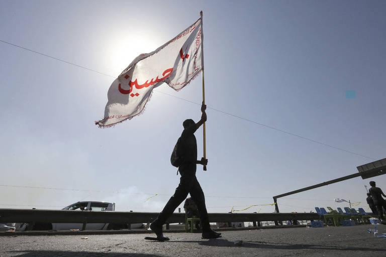 Homem carrega bandeira enquanto caminha