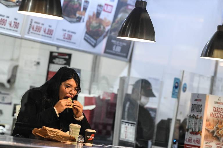 Uma mulher come em um restaurante. Ela está sentada e leva um lanche até a boca