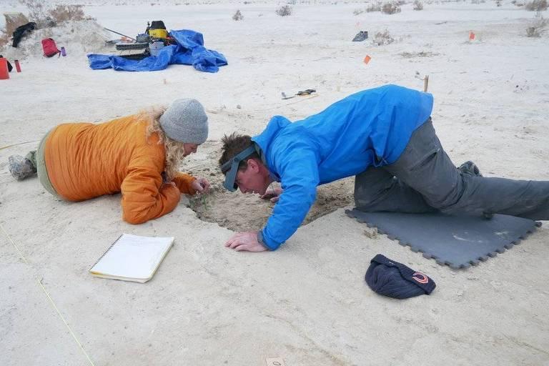 uma mulher e um homem estão agachados observando sedimentos antigos