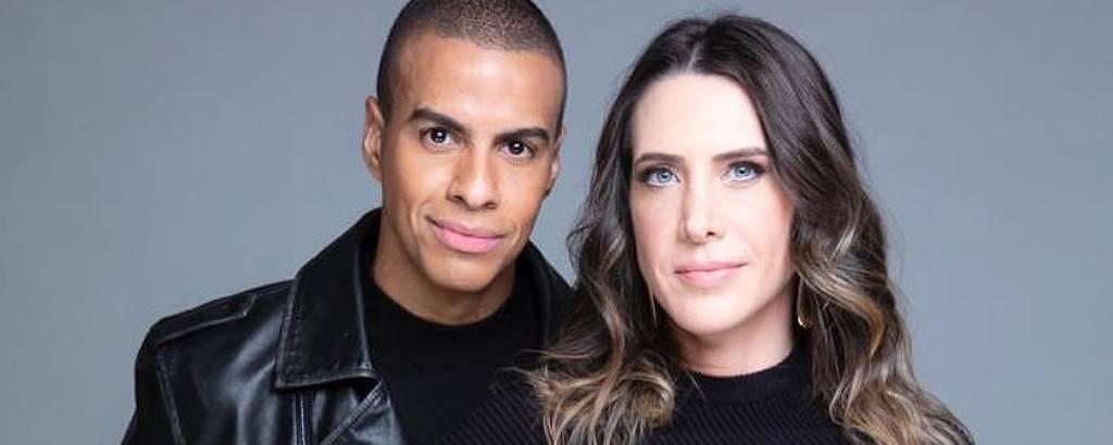 Homem negro e mulher branca de olhos claros ambos vestindo roupas pretas
