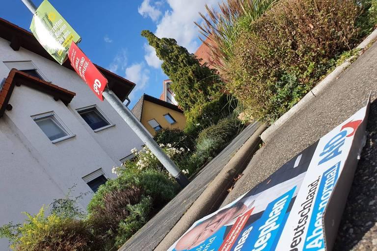cartaz de papelão azul em primeiro plano no chão e, em poste, dois cartazes, um verde e um vermelho