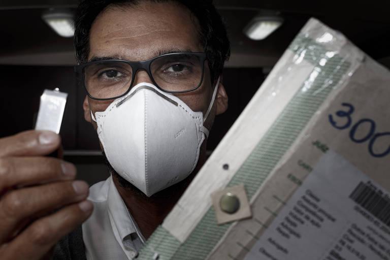 Um homem de óculos, máscara branca, segurando um pendrive numa mão e um processo na outra