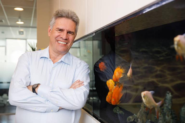 homem branco em frente a um aquário