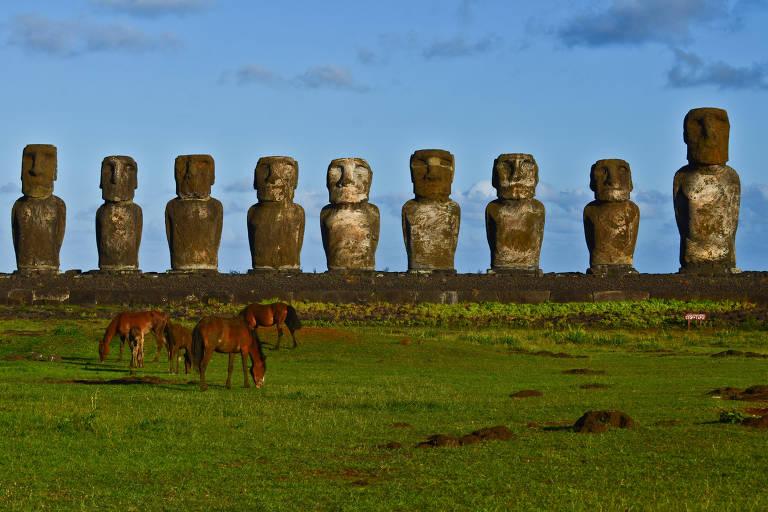 nove grandes estátuas em forma de homem, ao fundo, e três cavalos mais à frente, pastando