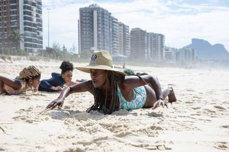 Foto mostra uma mulher negra deitada sobre a prancha na areia da praia, sendo imitada por duas crianças