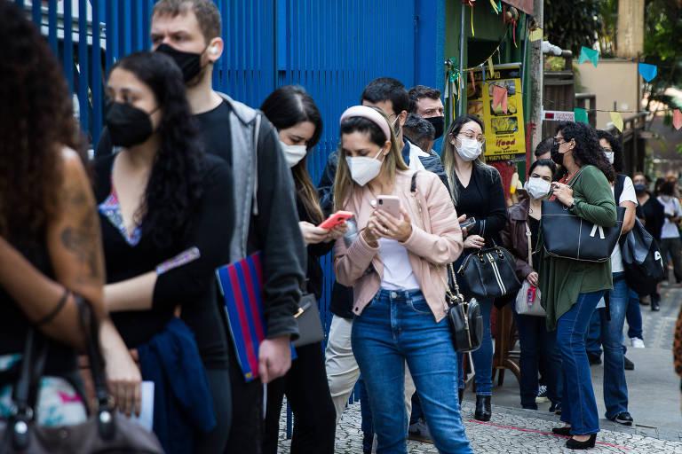 Fila de pessoas de máscaras no que parece ser uma calçada; à esquerda da foto, uma grade azul