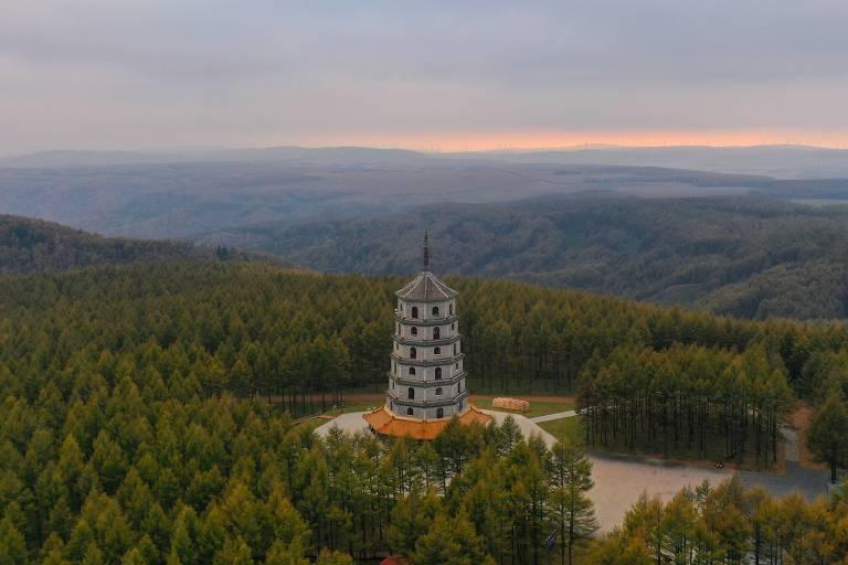 Foto aérea mostra a floresta do Parque Nacional Saihanba, localizado na província de Hebei, no norte da China. Há, no meio da imagem, a torre Saihan, e o céu está levemente nublado.