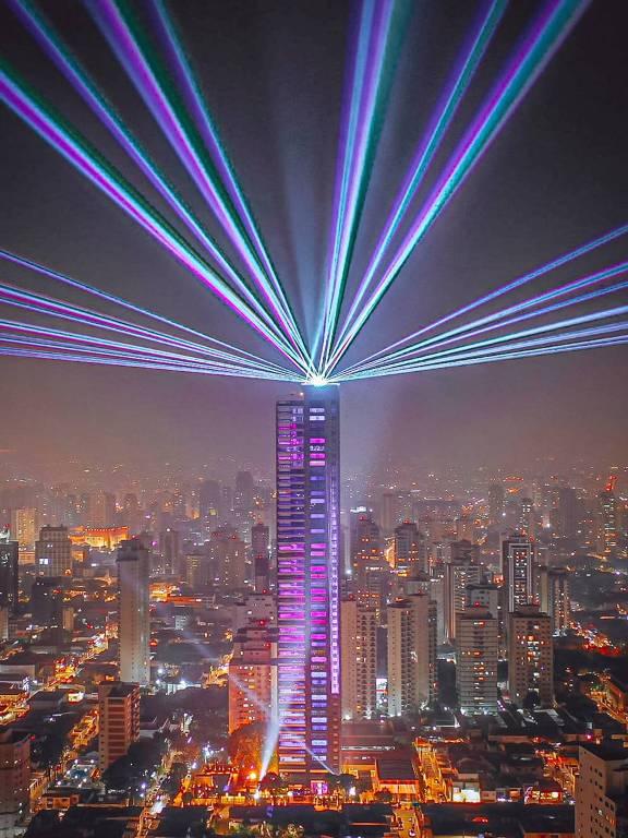 Foto noturna de prédio iluminado, com canhão de luzes no topo