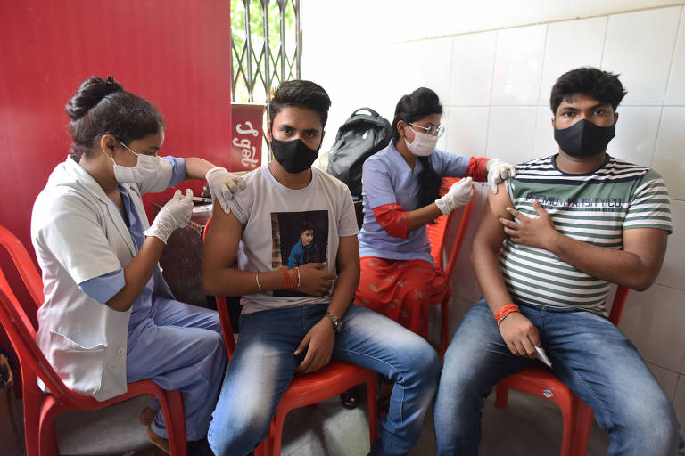 Quatro pessoas estão sentadas em cadeiras vermelhas; duas mulheres e dois homens, todos de máscara. As mulheres aplicam a vacina nos braços direitos dos homens