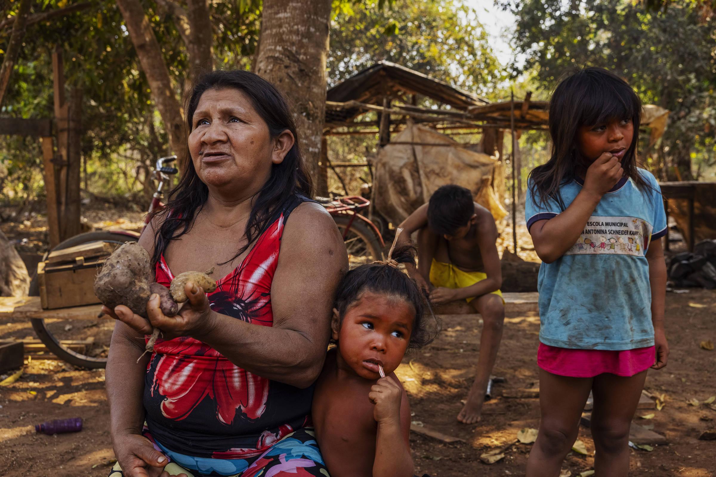 Lucibete Iurici mostra a sua produção de tubérculos, cercada pelos seus netos, na aldeia 13 de Maio na Terra Indígena Irantxe
