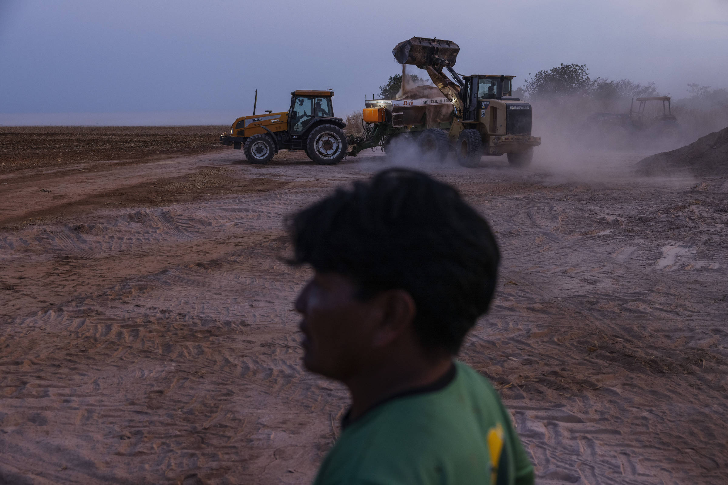 Manokis responsáveis pela lavoura mecanizada observam a movimentação de tratores jogando calcário para equilibrar o solo na preparação para o plantio