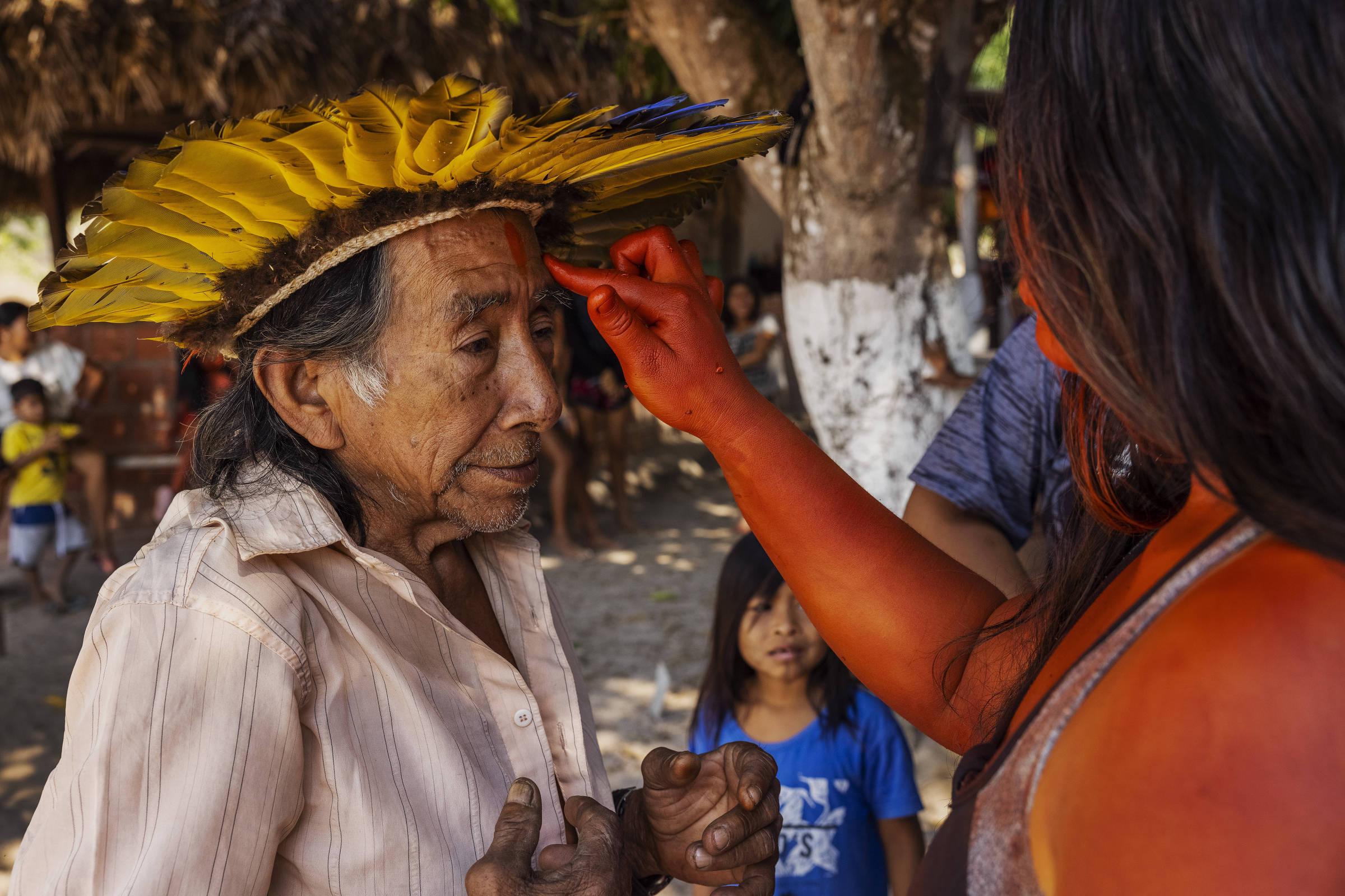 Jovem pinta o rosto do cacique Manoel Kanunxi, 71, antes de uma apresentação cultural do povo manoki