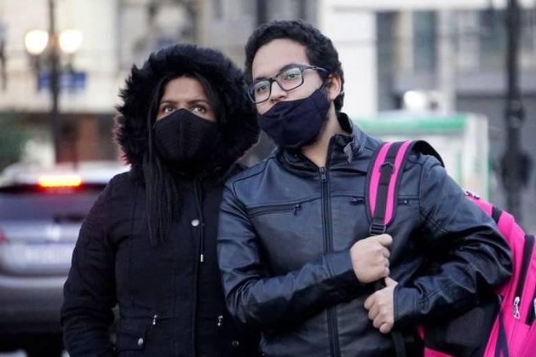 jovens na rua vestem casaco e se protegem do frio