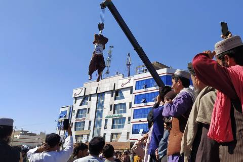 EDITORS NOTE: Graphic content / A dead body (top) displayed in a public area is hanging on a crane in Herat on September 25, 2021, after Taliban killed four kidnappers during a shootout and hanged them, a senior official said. (Photo by - / AFP)