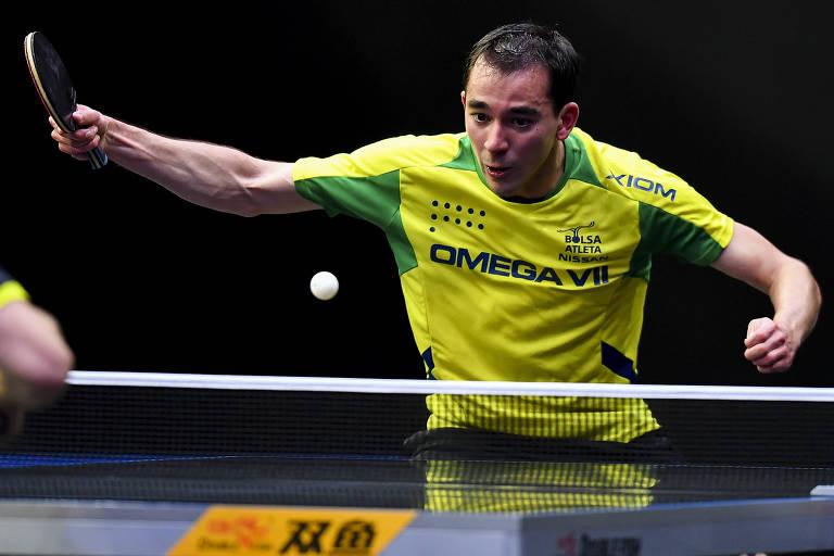 Homem de blusa amarela joga tênis de mesa