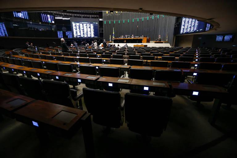 Plenário quase vazio; em primeiro plano, diversas cadeiras praticamente no escuro