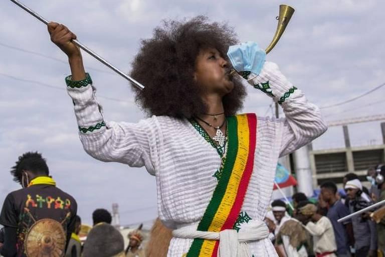 mulher toca instrumenyo de sopro e tem uma faixa com as cores verde, amarela e vermelha da bandeira etíope