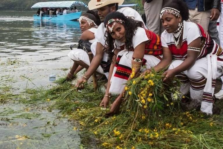 jovens jogam flores em um rio