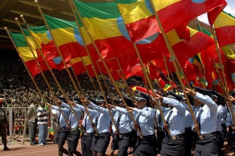miliatares marcham com estandartes da bandeira