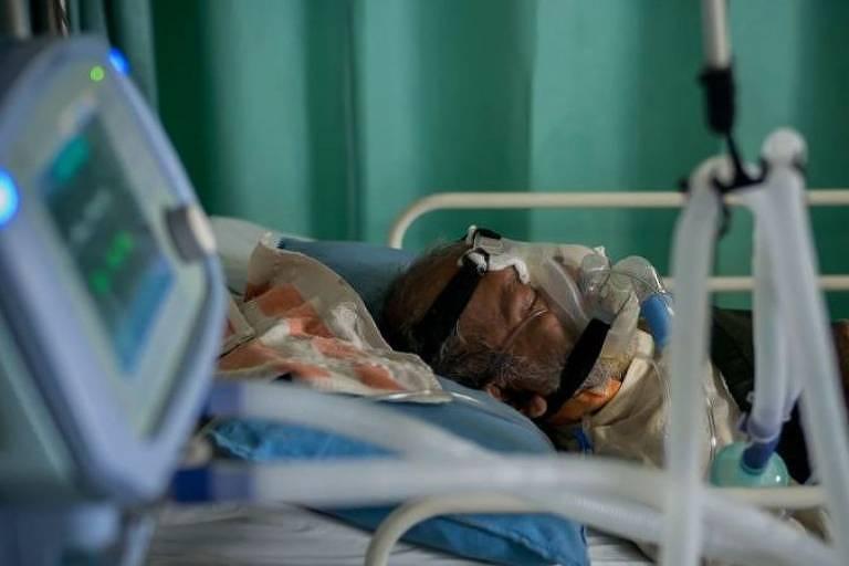 Homem intubado em maca, com maquinário médico em volta