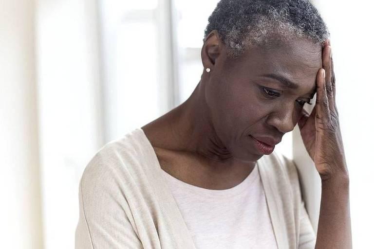 Imagem em primeiro plano mostra uma mulher negra idoso com semblante de preocupada. Ele leva uma das mãos a cabeça que está levemente abaixada.