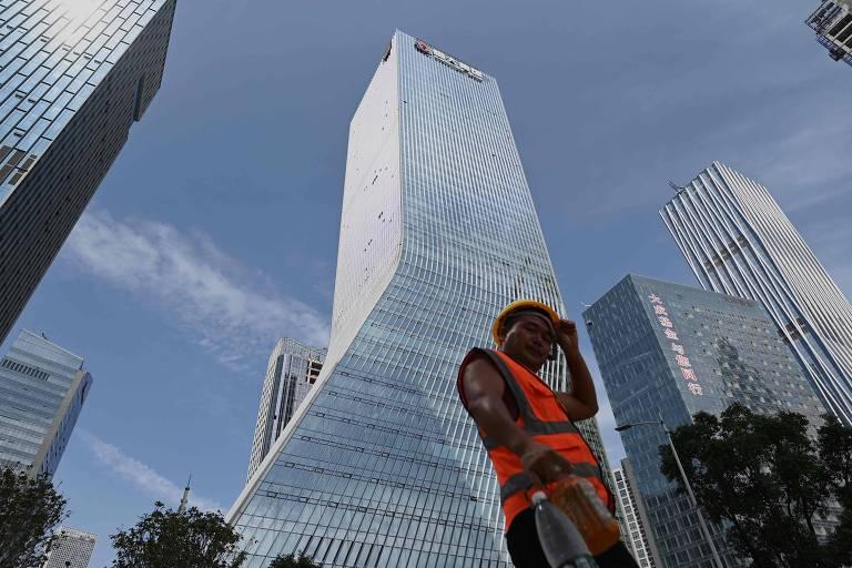 Trabalhador diante da sede da Evergrande, em Shenzhen, no sudeste China