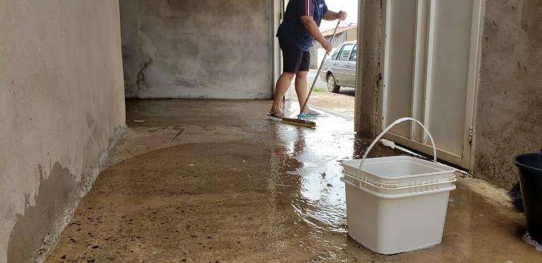 Moradora da Vila Imperador, que está sem abastecimento nesta segunda-feira (27) por conta do racionamento da Sabesp em Franca, utiliza água que armazenou da chuva para limpar garagem após tempestade de poeira no dia anterior.