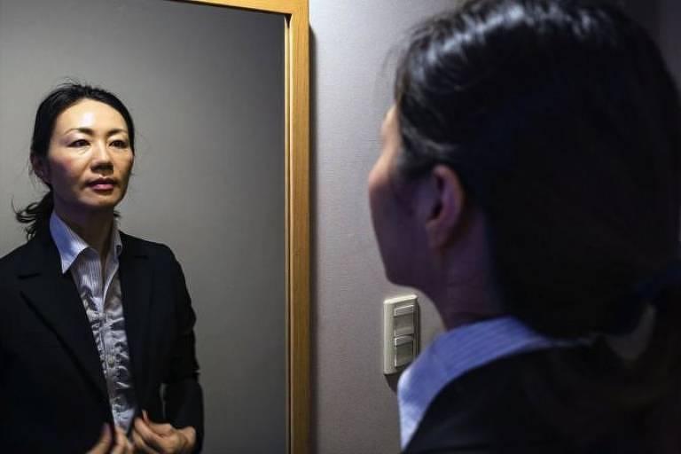 Mulher com roupa social se olha no espelho
