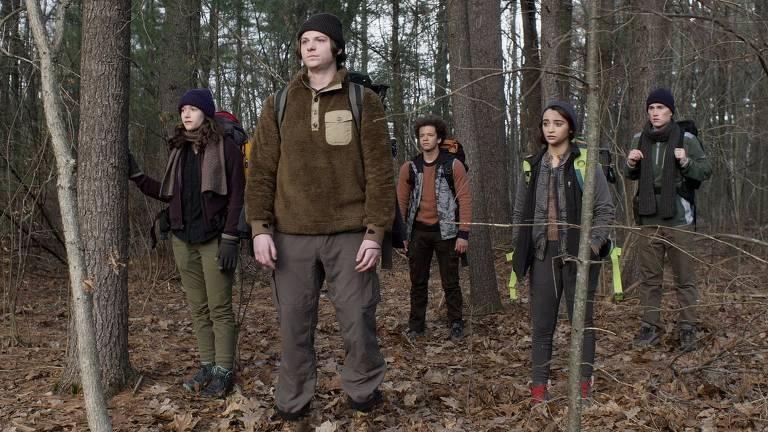 Cinco jovens no meio do mato observam a diante
