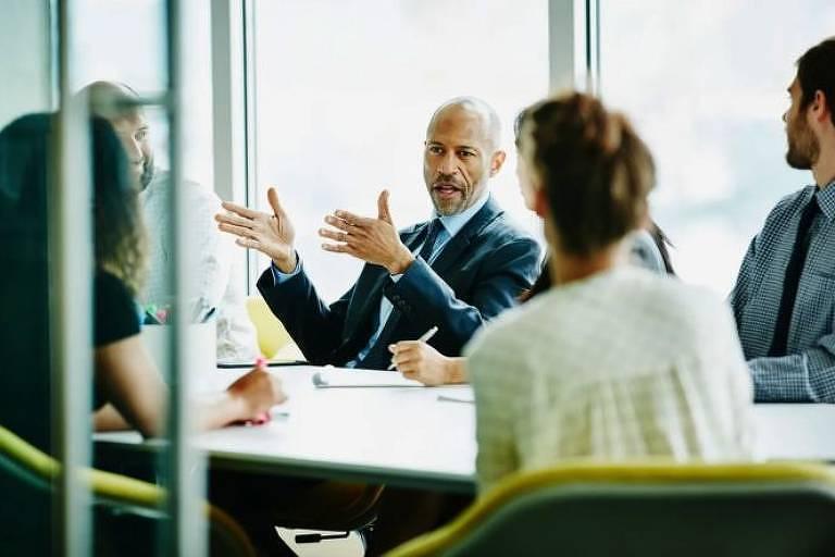 Homem fala durante reunião de trabalho