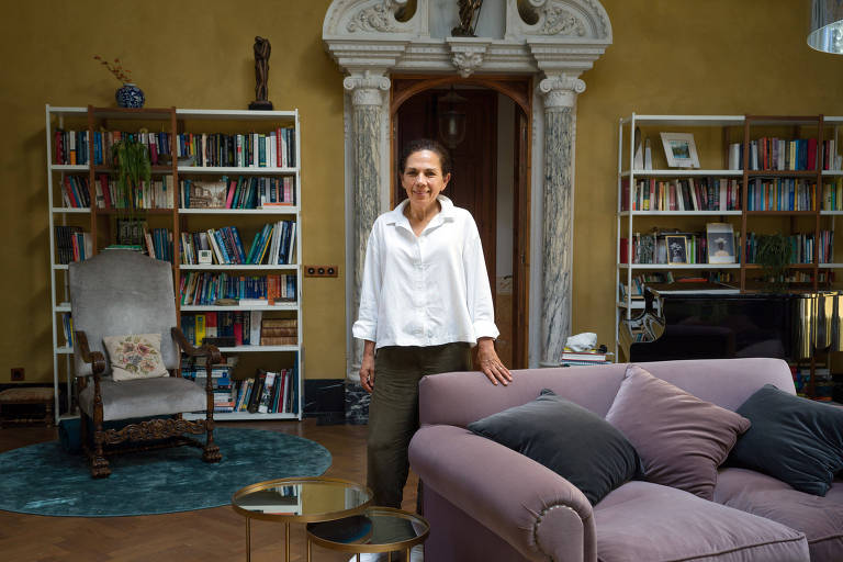 Mulher veste uma camisa branca e calças. Está em sua casa em Barcelona, na Espanha