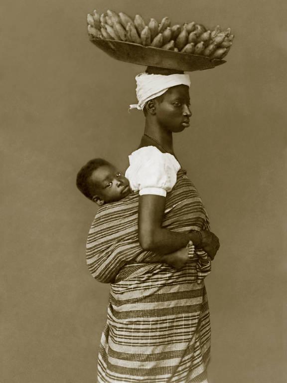 Retrato de mulher negra com criança às costas e cesto de bananas na cabeça