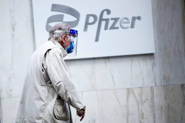 Homem com escudo facil e máscara passa em frente ao logo da Pfizer