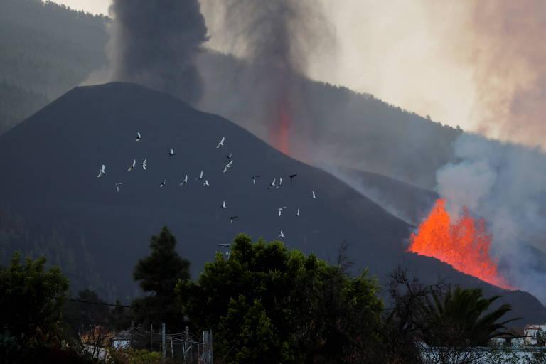 Fumaça se ergue de cume de vulcão, enquanto incêndio continua na base do monte