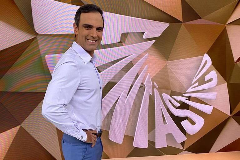 Homem vestindo calça jeans e camisa branca com sapatos sociais marrom escuro, sorrindo virado para o lado direito, com as mãos na cintura, dentro do estúdio do programa Fantástico, posando frente a um painel em tons de marrom