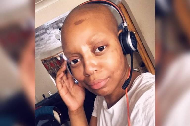 imagem em close mostra o rosto de uma mulher negra careca usando fone de ouvido