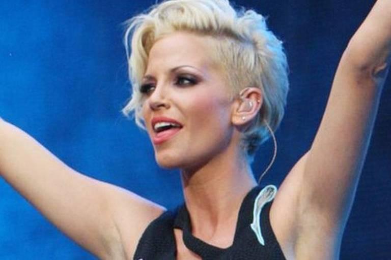 imagem em primeiro plano mostra mulher loira de cabelo curto com os braços erguidos
