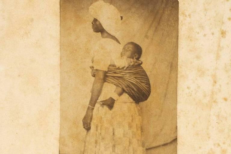 uma mulher negra está em pé com uma criança presa a suas costas por um tecido.