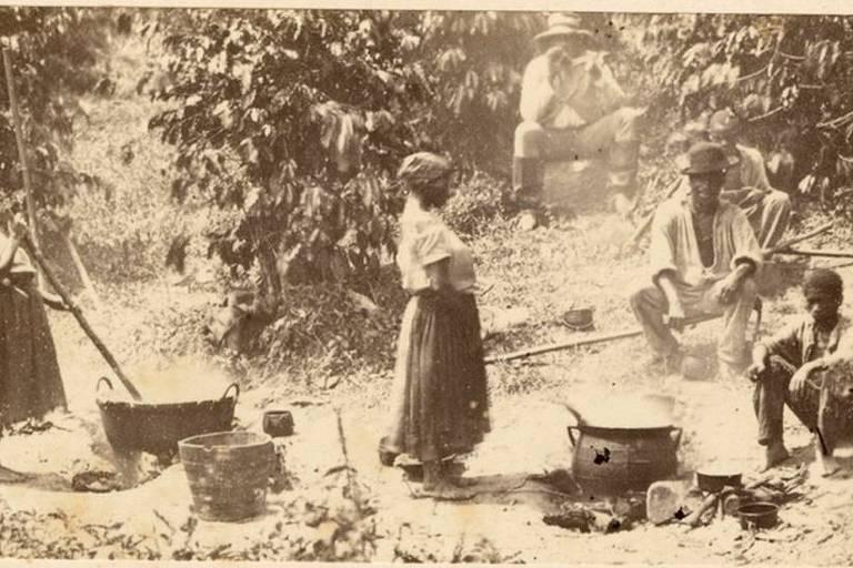 imagem em preto e branco mostra duas mulheres negras em pé e três homens senrtados. Ao redor deles há vegetação