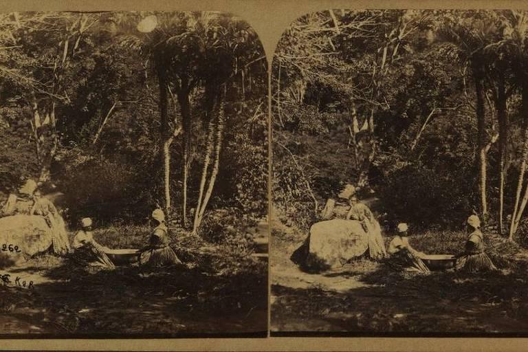 imagem em preto e branco mostra duas mulheres negras sentadas no chão e uma mulher branca encostada em uma pdra. Ao redor delas há vegetação